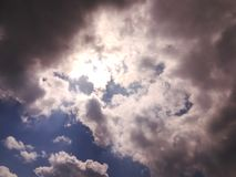 Sky, clouds and sunlight. Sun light is diffused thorough black and white clouds royalty free stock photos