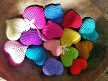 Sun light on falling flower and leaf on colourful hearts in wooden tray in the garden Stock Photography