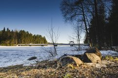 Sun light illuminated stone in front of a frozen lake with birch pine trees around while branches hanging from the blue sky royalty free stock photos