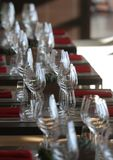 Sun light illuminates a wooden table full of empty glasses and white candles. Sun light illuminates a wooden table full of empty glasses stock photography