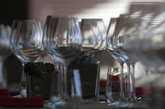 Sun light illuminates a wooden table full of empty glasses and white candles. Sun light illuminates a wooden table full of empty glasses stock photos