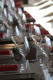 Sun light illuminates a wooden table full of empty glasses and white candles. Sun light illuminates a wooden table full of empty glasses stock photo