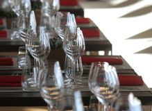 Sun light illuminates a wooden table full of empty glasses and white candles. Sun light illuminates a wooden table full of empty glasses royalty free stock photos