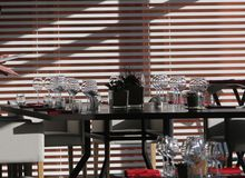 Sun light illuminates a wooden table full of empty glasses and white candles. Sun light illuminates a wooden table full of empty glasses stock images