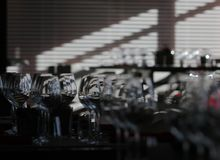 Sun light illuminates a wooden table full of empty glasses and white candles. Sun light illuminates a wooden table full of empty glasses royalty free stock image