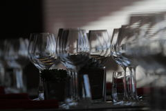 Sun light illuminates a wooden table full of empty glasses and white candles. Sun light illuminates a wooden table full of empty glasses stock image
