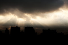 Sun light shine through dark cloud with silhouette of building Royalty Free Stock Photography