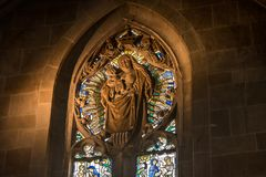 Spiritual Light on church window. Sun light shines on a stone statue engraved on a church stained glass window stock photography
