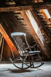 Sun light shines through window on a rocking chair in the attic room. Lonely and empty room feeling. Early morning with sun rays Royalty Free Stock Photo