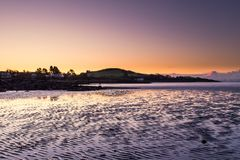The sun lights up the sky behind the hills along the South Scottish coast at Rockcliffe stock images