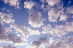 Sun-lit Hintergrund des bewölkten blauen Frühlingshimmels Stockbilder