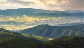 Sun lit valley in afternoon. Beautiful mountainous landscape and cloudy sky in golden light. lovely scenery after the storm. view from the top of a hill Stock Image