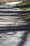 Sun lit wooden walk path winding far away Stock Photo