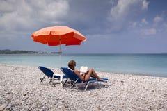 Sun longer and umbrella on empty beach Royalty Free Stock Image