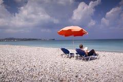 Sun longer and umbrella on empty sandy beach Royalty Free Stock Photos