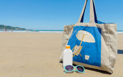 Sun lotion and sunglasses in the beach Stock Image
