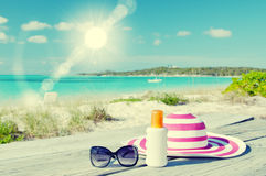 Sun lotion, sunglasses and hat Stock Photos