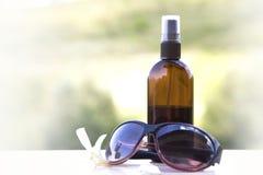 Sun lotion and sunglasses Stock Image