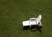 Sun lounger. White sunlounger on green grass Stock Images