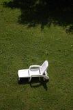 Sun lounger. White sunlounger on green grass Stock Photo