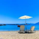 Sun Lounger och ett slags solskydd på en strand Fotografering för Bildbyråer