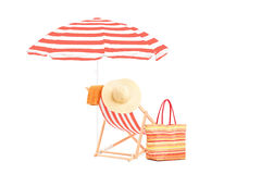 Sun lounger with orange stripes, umrella and summer accessories Stock Image