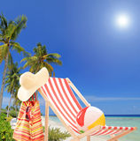 Sun lounger at sunny day on a tropical beach with palms Stock Images
