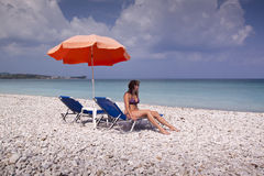 Sun lounger and umbrella on empty rock beach Royalty Free Stock Photography