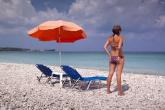 Sun lounger and umbrella on empty sandy beach Royalty Free Stock Photo