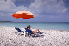 Sun lounger and umbrella on empty sandy beach Royalty Free Stock Image