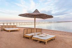 Sun lounger under the beach umbrella with view at the sea coast. Sunset on the beach. Wooden shore-arm over the sea Stock Images