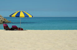 Sun lounger under an umbrella on the beach. Sun lounger under an a blue-yellow umbrella on an empty beach Stock Photo