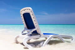Sun lounger in the water on the beach Stock Photo