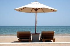 Sun Loungers. On a beach underneath a parasol royalty free stock photos