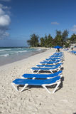 Sun loungers at Accra Beach Barbados. Row of vacant sun loungers lined up on Rockley Beach on the south coast of the Caribbean island of Barbados in the West royalty free stock photography