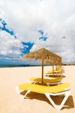 Sun Loungers At The Beach. With straw parasols stock photography