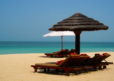 Sun Loungers on Beach. Sun Lounger Beds on a beach underneath different parasols Stock Photography