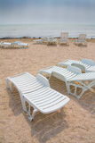 Sun loungers on beach. Vacant white sun loungers on sandy beach with sea in background royalty free stock image