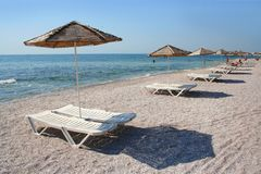 Sun loungers on beach. Pairs of sun loungers under parasols on sandy beach with sea in background royalty free stock photos