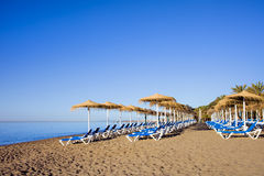 Sun Loungers on a Beach in Marbella. Sun loungers on a tranquil beach at the popular resort city of Marbella in Spain, Costa del Sol, Malaga province stock image
