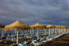 Sun Loungers on a Beach with Stormy Sky Royalty Free Stock Image