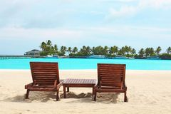 Sun loungers on beach. At sea resort royalty free stock photos