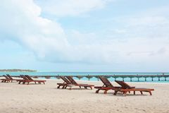 Sun loungers on beach. At sea resort stock images