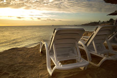 Sun loungers on the beach with sunset Stock Images