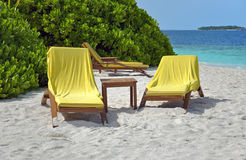 Sun loungers on beach of tropical island Royalty Free Stock Photos