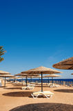 Sun loungers and a beach umbrella on a beach perfect vacation concept Stock Photos
