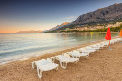Sun loungers and beach umbrellas on the beach,Makarska,Croatia,E. Morning on the beach,Makarska,Croatian Riviera,Dalmatia,Europe Royalty Free Stock Photography