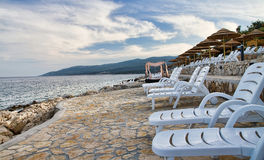 Sun loungers and beach umbrellas. Parasols and sun loungers on the deserted Istrian beach Stock Photography
