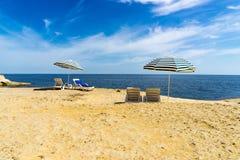 Sun loungers on a beach underneath a parasol Stock Image
