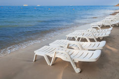 Sun loungers on the beach Stock Images